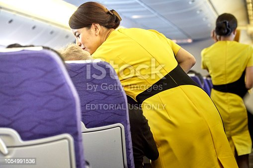 823006998 istock photo Airline nokscoot Interior of airplane with passengers on seats and stewardess in Yellow uniform at the aisle. 1054991536