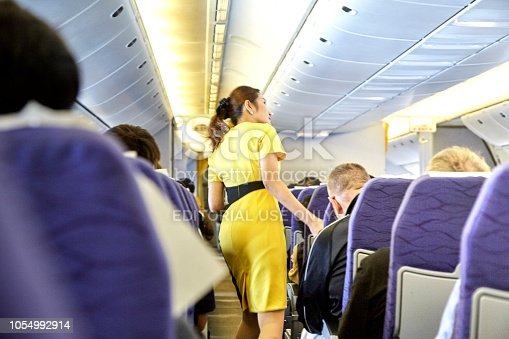 823006998 istock photo Airline nokscoot Interior of airplane with passengers on seats and stewardess in Yellow uniform at the aisle. 1054992914