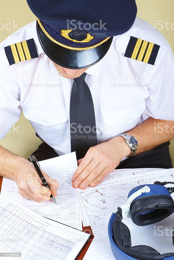 Airline pilot filling in forms royalty-free stock photo