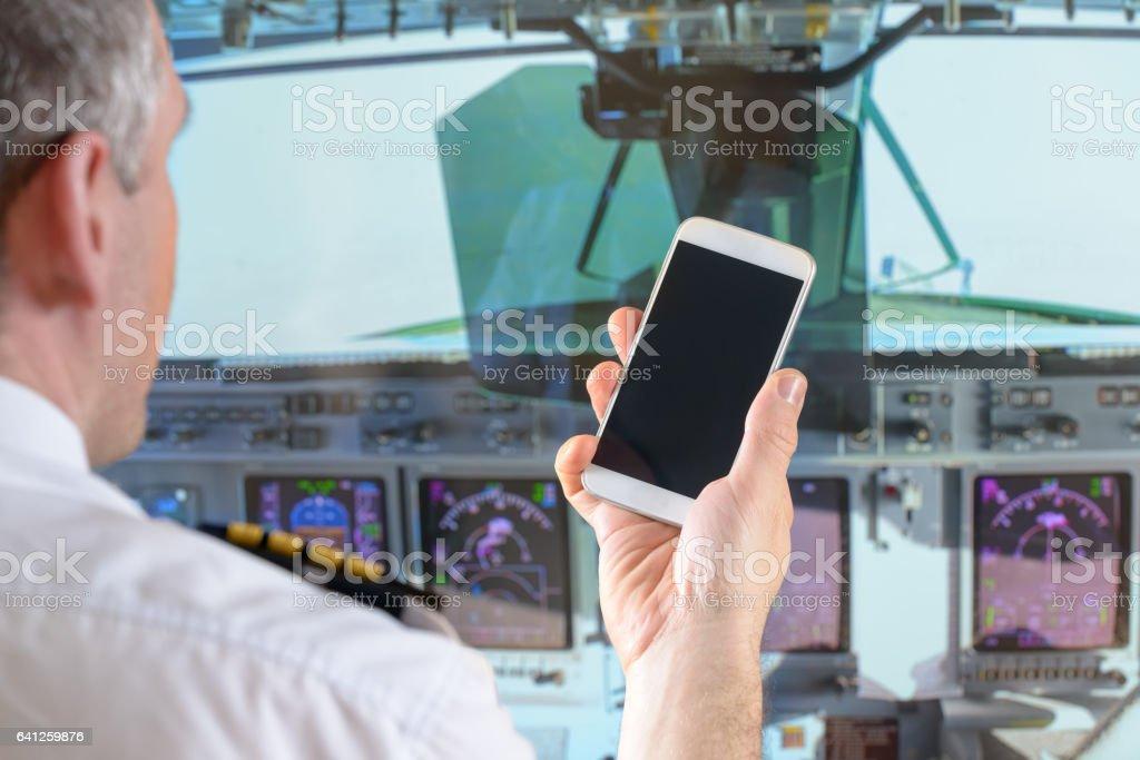Akıllı telefon kullanan havayolu pilotu stok fotoğrafı