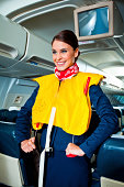 Beautiful flight attendant standing in an airplane and demonstrating a life jacket before taking off.