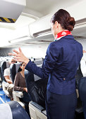 Back view of flight attendant standing in an airplane and demonstrating a emergency exits before taking off.