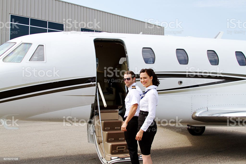 Airline staff turn before entering plane stock photo