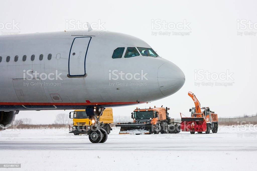 Airliner and snow removal equipment in a cold winter airport стоковое фото