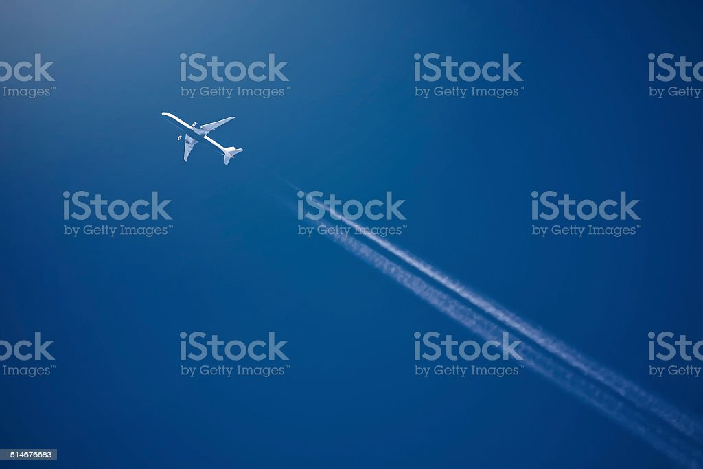 Airliner at high altitude with white condesation trails stock photo
