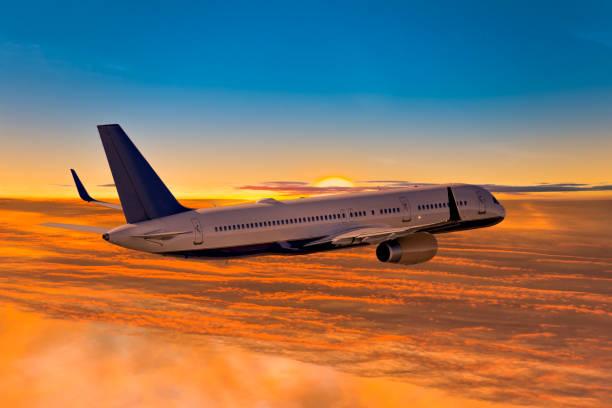Flugzeug fliegt über den Wolken bei Sonnenuntergang für Urlaub – Foto