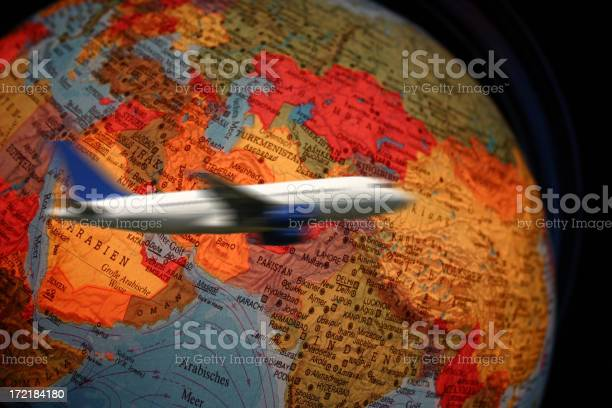 Airliner Flying Around Globe Stock Photo - Download Image Now