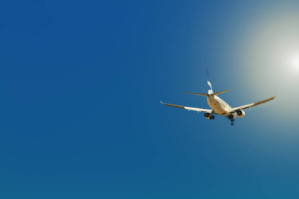 Airliner flying with sun in the background stock photo