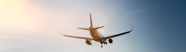 passagierflugzeug beim landeanflug zum flughafen bei sonne in der sonne - tim siegert stock-fotos und bilder