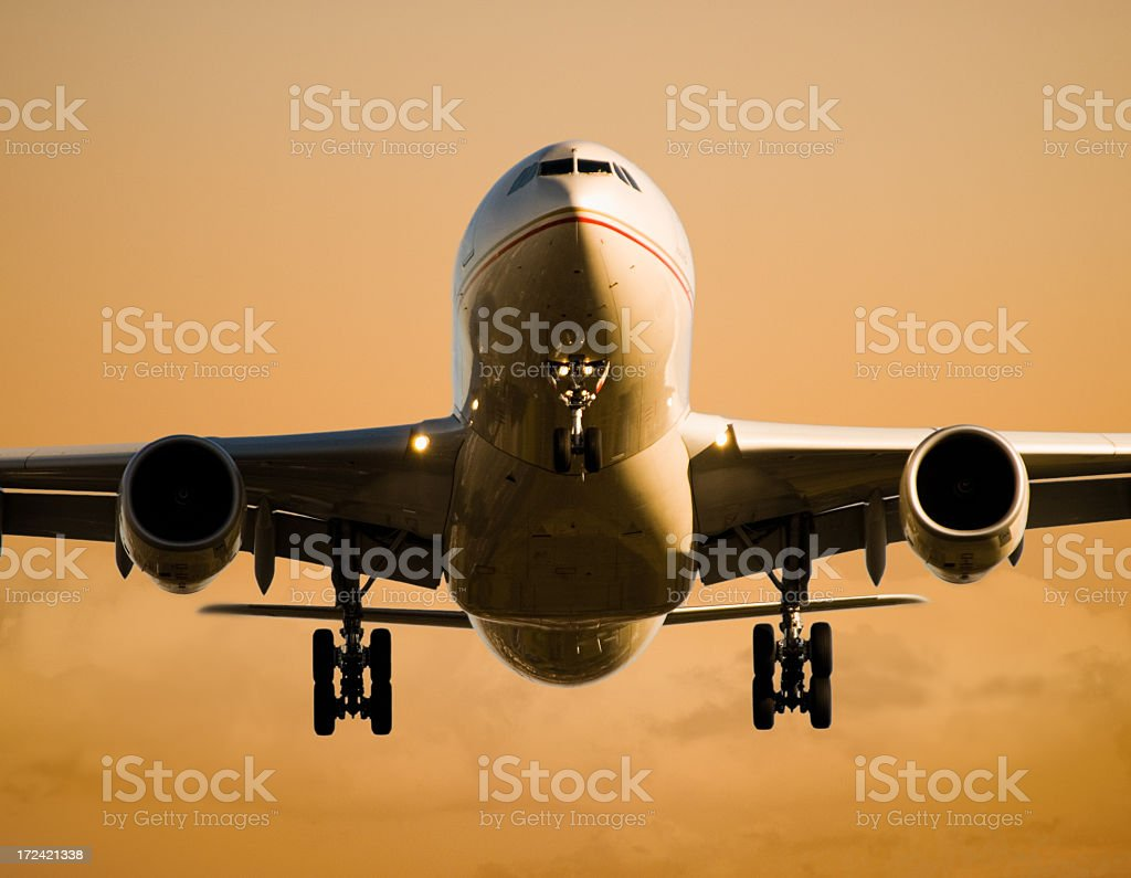 Airliner landing at Sunset stock photo