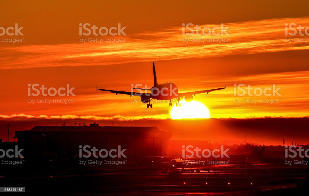 Airliner lands to runway late evening sunset stock photo
