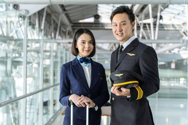 エア旅客機のパイロットとエアホステスが空港ターミナルに立ち、笑顔でカメラを見ています。航空輸送コンセプトの航空会社のビジネス、仕事とキャリア。 - スチュワーデス 日本人 ストックフォトと画像