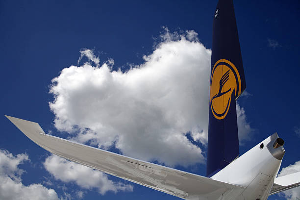 Airliner tail wing in blue summer sky with puffy clouds stock photo