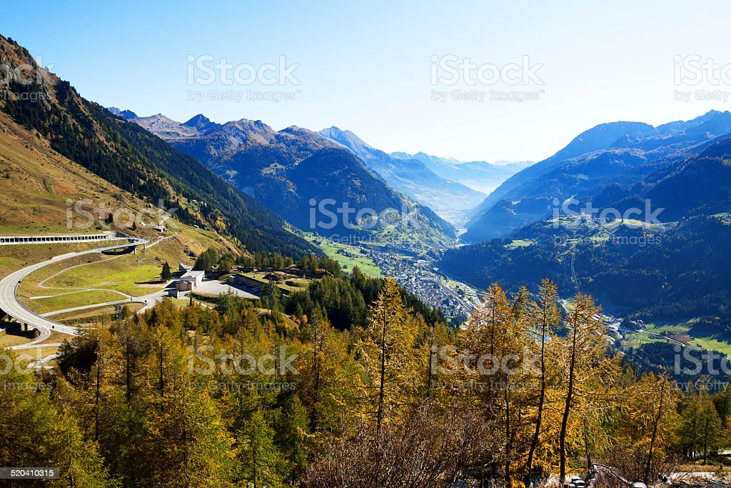 Airolo seen from St. Gotthard Aerial view into valley from St. Gotthard, Airolo is down in valley. Pass road is winding up at left side. Aerial View Stock Photo