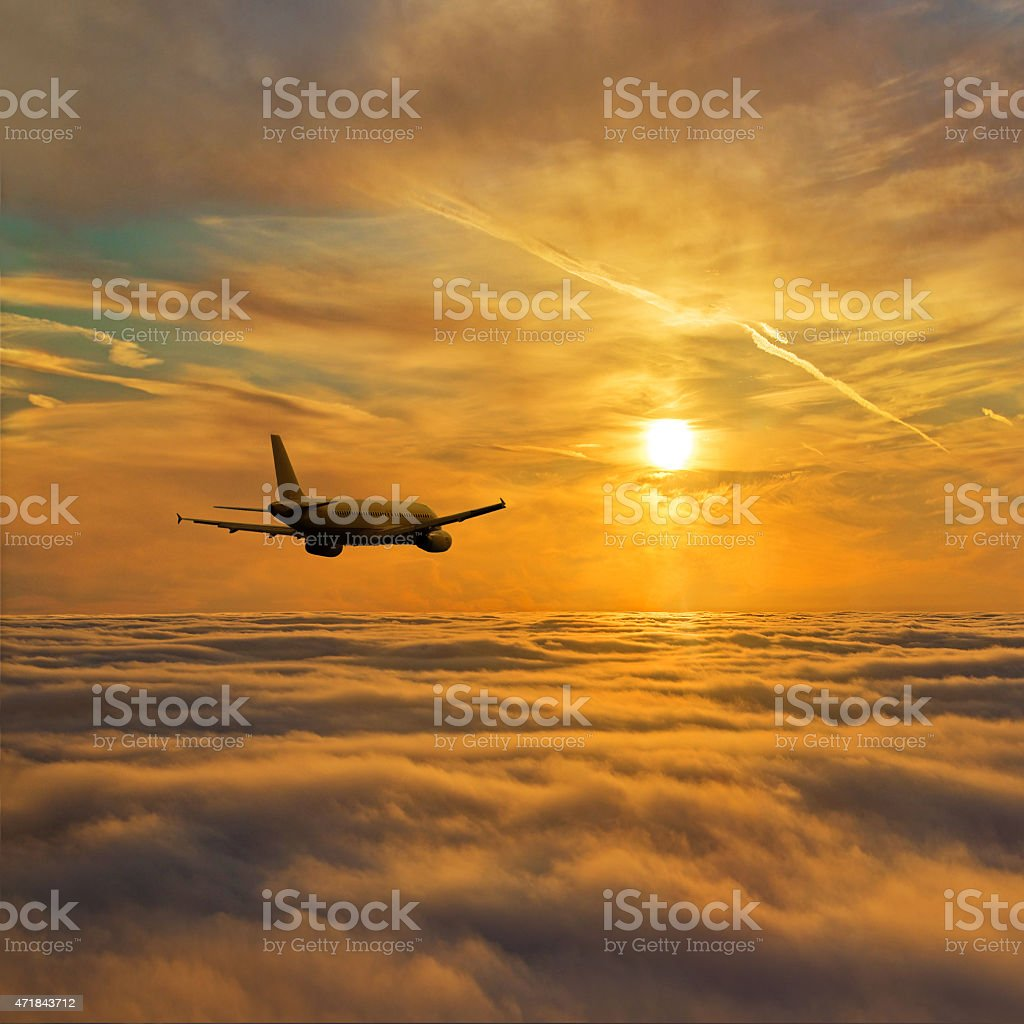 Airplain flight above clouds against golden sunset sky stock photo