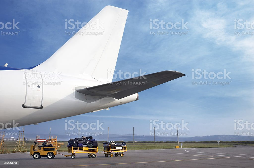 airplain tale and luggage cart royalty-free stock photo