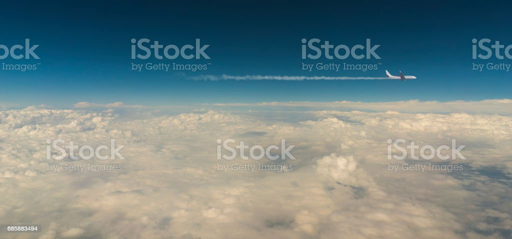 Airplane above clouds with copyspace stock photo