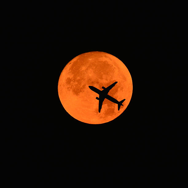 airplane across a full moon stock photo