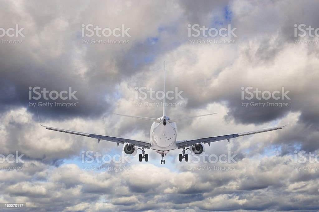 Airplane against cloudy sky stock photo