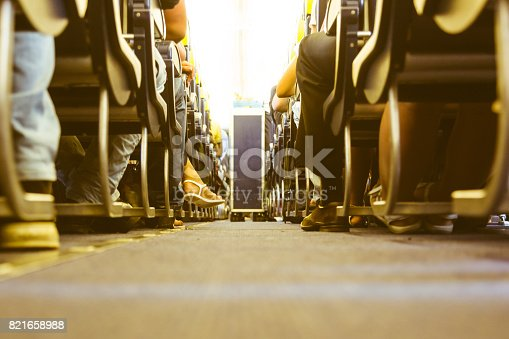 istock Airplane aisle with passengers feet on both sides 821658988
