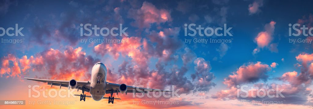 Airplane and beautiful sky. Landscape with passenger airplane is flying in the blue sky with red, purple and orange clouds at sunrise. Travel. Passenger airliner. Commercial aircraft. Private jet stock photo