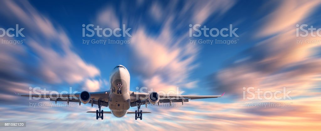 Airplane and beautiful sky with motion blur effect. Landscape with passenger airplane is flying in blurred blue sky with colorful clouds at sunset. Passenger airliner. Commercial aircraft. Private jet stock photo