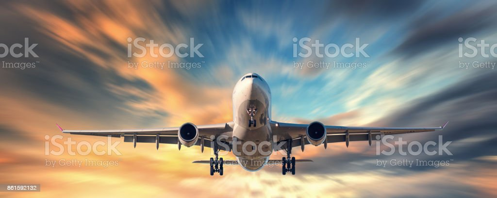 Airplane and beautiful sky with motion blur effect. Landscape with passenger airplane is flying in blurred blue sky with yellow clouds at sunset. Passenger airliner. Commercial aircraft. Private jet stock photo