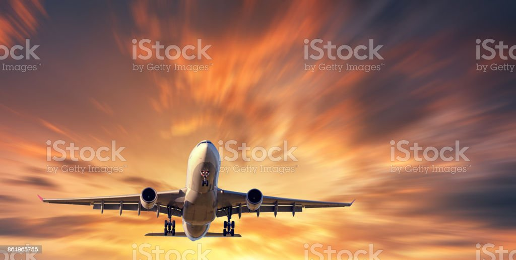 Airplane and beautiful sky with motion blur effect. Landscape with passenger airplane is flying in blurred orange sky with clouds at sunset. Passenger airliner. Commercial aircraft. Private jet stock photo