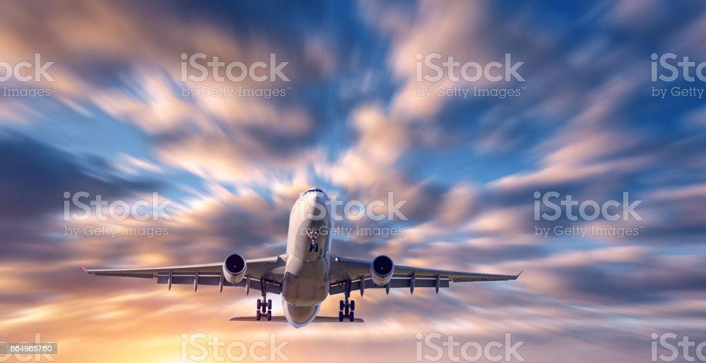 Airplane and beautiful sky with motion blur effect. Landscape with flying passenger airplane and blurred blue sky with colorful clouds at sunrise. Passenger airliner. Commercial aircraft. Private jet stock photo