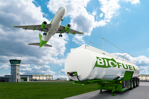Airplane and bioguel tank trailer on the background of airport. New energy sources