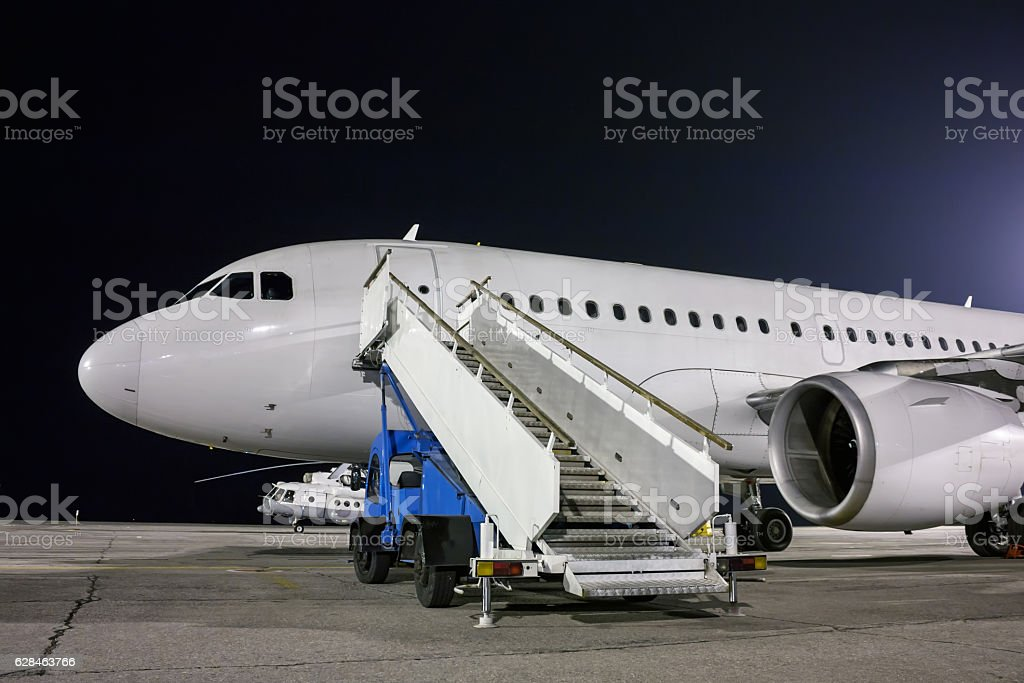 Airplane and passenger boarding steps at the night airport apron royaltyfri bildbanksbilder