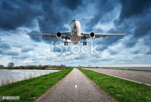 816320512 istock photo Airplane and road. Landscape with passenger airplane is flying over the asphalt road against cloudy sky, green grass. Journey. Passenger airliner is landing on the runway. Commercial plane and highway 816320472