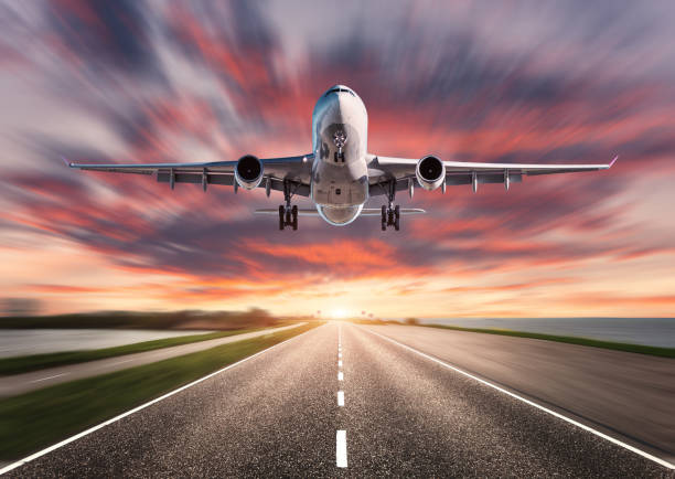 airplane and road with motion blur effect at sunset. landscape with passenger airplane is flying over asphalt road and colorful sky. commercial plane is landing. aircraft with blurred background - den belitsky foto e immagini stock
