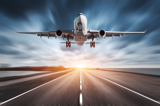 istock Airplane and road with motion blur effect at sunset. Landscape with passenger airplane is flying over the asphalt road and cloudy sky. Commercial plane is landing. Aircraft with blurred background 816320540