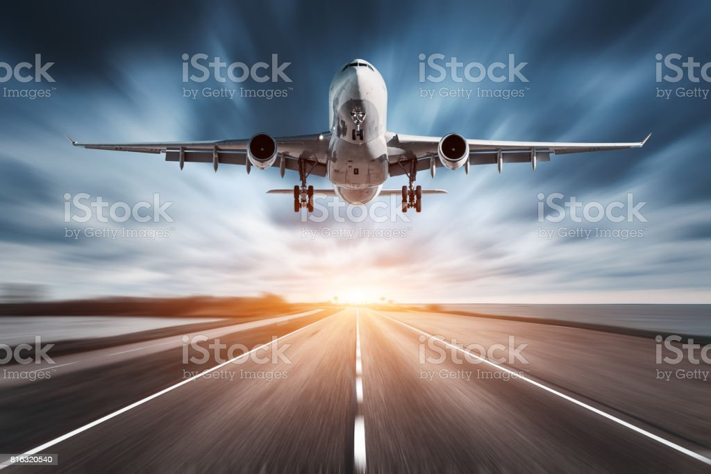 Airplane and road with motion blur effect at sunset. Landscape with passenger airplane is flying over the asphalt road and cloudy sky. Commercial plane is landing. Aircraft with blurred background - foto stock