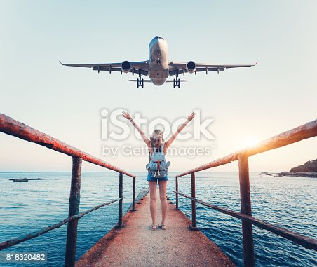 istock Airplane and woman at sunset. Summer landscape with girl standing on the sea pier with raised up arms and flying passenger airplane. Woman and landing commercial plane in the evening. Lifestyle 816320482