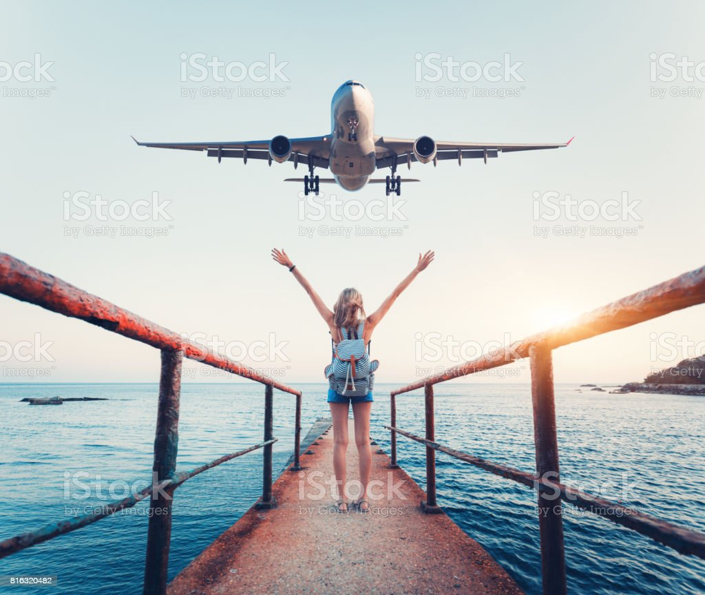 Airplane and woman at sunset. Summer landscape with girl standing on the sea pier with raised up arms and flying passenger airplane. Woman and landing commercial plane in the evening. Lifestyle stock photo
