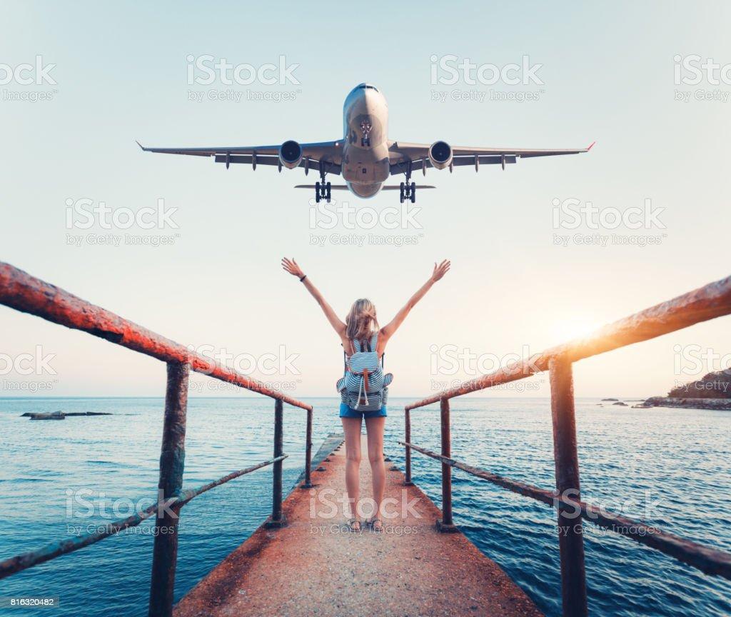 Avión y la mujer al atardecer. Paisaje de verano con chica de pie en el muelle de mar con los brazos levantados hacia arriba y avión de pasajeros del vuelo. Mujer y aterrizaje avión comercial por la noche. Estilo de vida - foto de stock
