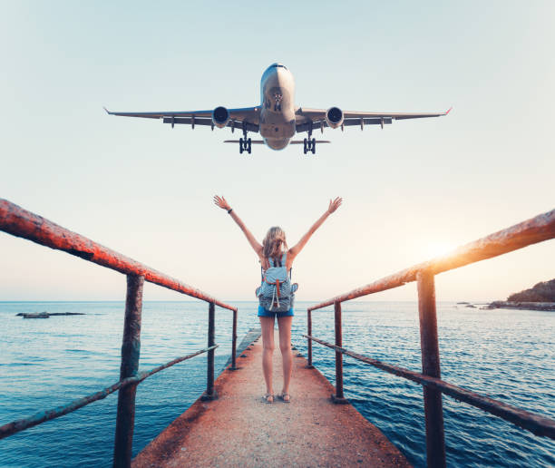 airplane and woman at sunset. summer landscape with girl standing on the sea pier with raised up arms and flying passenger airplane. woman and landing commercial plane in the evening. lifestyle - travel destinations stock photos and pictures