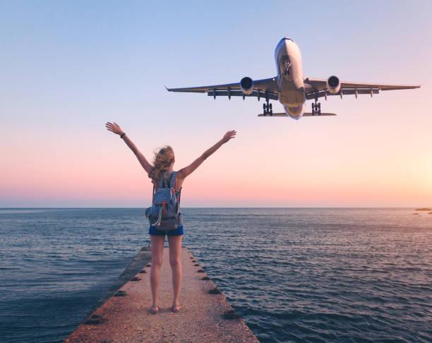 Avião e a mulher ao pôr do sol. Paisagem de verão com menina em pé no cais do mar com os braços erguidos acima e voar o avião de passageiros. Mulher e aterragem de avião comercial no crepúsculo. Estilo de vida e viagem - foto de acervo