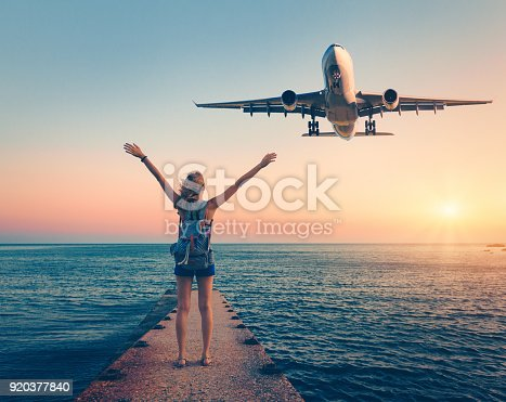 istock Airplane and woman at sunset. Summer landscape with girl standing on the sea pier with raised up arms and flying passenger airplane. Woman and landing commercial plane in the dusk.Lifestyle and travel 920377840