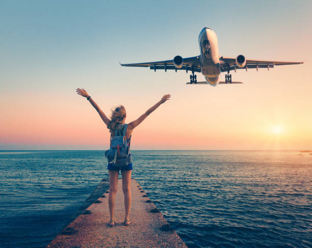 airplane and woman at sunset. summer landscape with girl standing on the sea pier with raised up arms and flying passenger airplane. woman and landing commercial plane in the dusk.lifestyle and travel - den belitsky foto e immagini stock