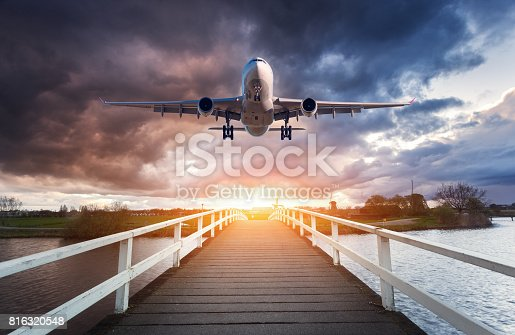816320512 istock photo Airplane and wooden bridge. Landscape with passenger airplane is flying over the wooden walkway against overcast sky at sunset. Journey. Passenger airliner is landing. Commercial plane and path 816320548
