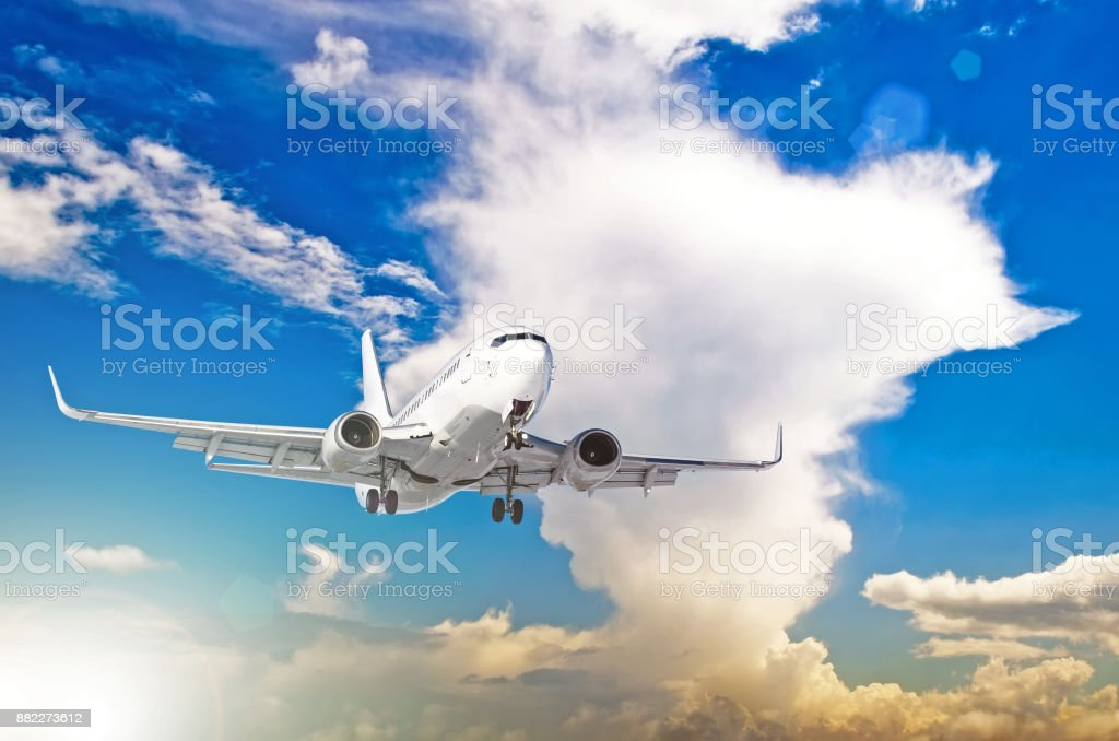 Airplane at fly on the sky with cumulus clouds sunset. stock photo