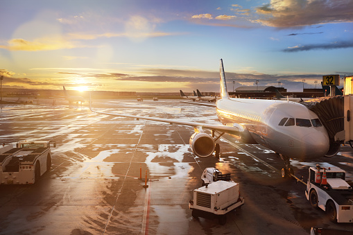 Airplane being preparing for takeoff at terminal gate in international airport at sunrise