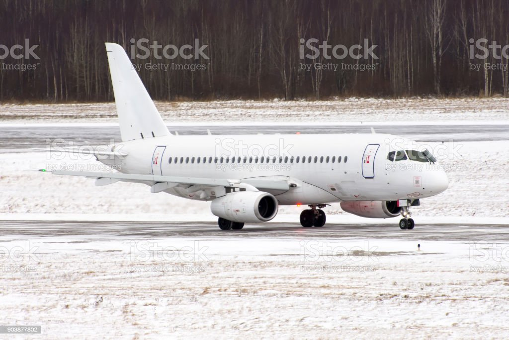 Airplane at the airport in a snow storm and poor visibility. stock photo