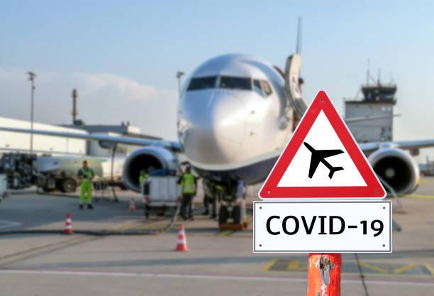 avión en la señal de aviso del aeropuerto coronavirus - avión fotografías e imágenes de stock