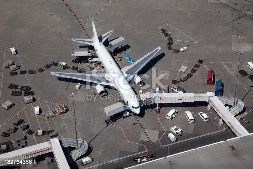 A large passenger airplane being readied for departure.  Aerial view.