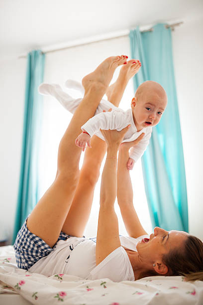 Airplane baby Mother is lifting baby above using her hands and legs while lying on the bed family having fun on the bed lifting legs stock pictures, royalty-free photos & images