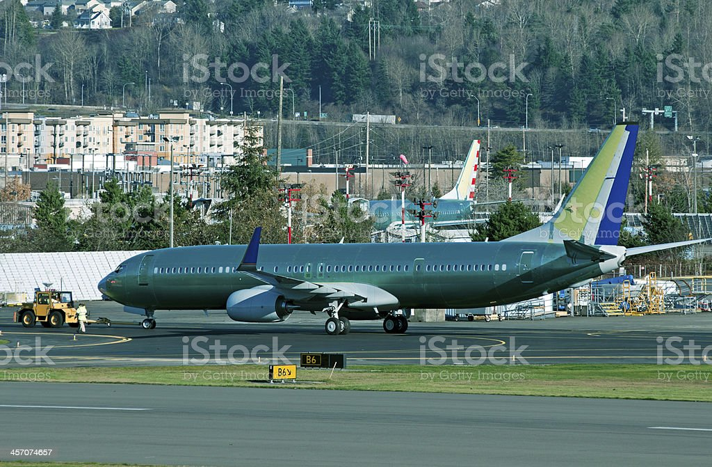 Airplane Being Towed To End Of Runway At Airport Stock Photo